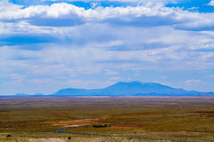 Mountains in the Distance. The landscape around Meteor Crater is fields of grass with some mountains in the distance and then there`s an area of red rock and royalty free stock image