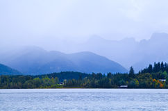 Mountains in fog by lake Stock Image