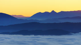 Mountains with fog at sunrise. Mountains with fog at the sunrise Royalty Free Stock Photos