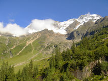 Mountains and Forests of Swiss Alps. Snow-capped mountains in Jungfrau region of Swiss Alps Stock Photo