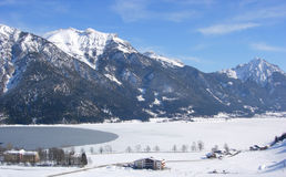 Mountains, frozen lake and village. Mountain backdrop, frozen lake and ski village Royalty Free Stock Images
