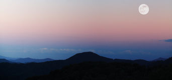 Mountains with full moon. The mountains at dusk with a bright full moon Royalty Free Stock Photos