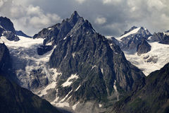 Mountains with glacier in clouds before rain Stock Photo