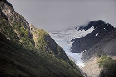 Mountains and glaciers of Alaska. Dramatic sky and mysterious fog over the wooded slopes of Alaska Stock Image
