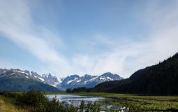 Mountains and glaciers surround lake in valley in  Alaska wilderness Royalty Free Stock Photos