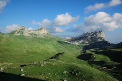 Mountains and grassland - The Durmitor Mountains, Dinaric Alps. The Durmitor Mountains, Dinaric Alps, infinity green pastures with Shepherd`s huts, grey high royalty free stock images