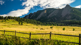 Mountains with grassy fields and a fence. Taken in Chautauqua Park in Boulder, CO Stock Image