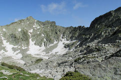 Mountains gray rock summit during the sunny day with clear blue sky Stock Images