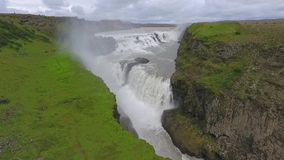 Mountains with greenery surround the waterfall in Iceland. Andreev. stock video footage