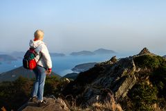 Mountains with heavy backpack Travel Lifestyle wanderlust adventure concept vacations. Woman hiking at sunset mountains with heavy backpack Travel Lifestyle stock image