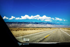 Mountains and highway through a car window Royalty Free Stock Photos