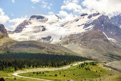 Mountains with ice field next to road with buses going to Columbia Icefield in Jasper National Park, Alberta, Canada. High mountains with ice field next to road stock photo