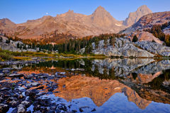 Mountains Illuminated by Sunrise Reflected in an Alpine Lake. Stock Photos