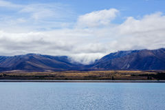 Mountains immersed in clouds. Symmetric hills immersed in clouds with lakefront Stock Images