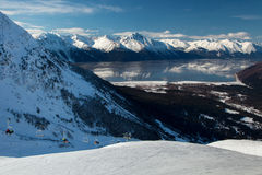 Alyeska View. The mountains of the Kenai Peninsula reflect in the unusually calm waters of Turnagain Arm as skiers ride the lift to the top of the run at Alyeska stock photography