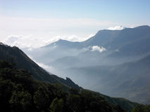 Mountains of Kerala with mist rising. Kerala is a state in South India which shares a border with Tamil Nadu. On that border is a mountain range with very deep stock images