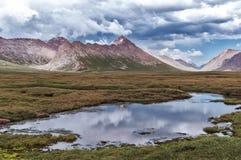 Mountains of Kyrgyzstan, mountain lake. Mountain lake, mountains, Kyrgyzstan, clouds in the sky Stock Photos