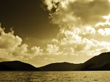 Mountains and lake. Sepia toned image of mountains lake and cloudy sky stock image
