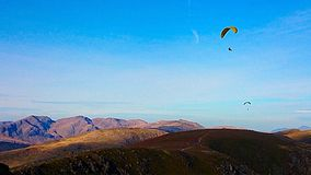 Mountains of the Lake District with Parachute Gliders. Two parachute gliders hovering above the colourful mountains of the Lake District Royalty Free Stock Photography