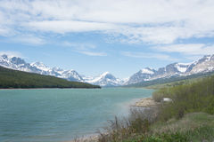 Mountains and Lake in Glacier National Park. A scenic view of snowcapped mountains in front of an aquamarine lake in Glacier National Park in Montana stock photo