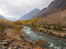Mountains And Lake In Golden Autumn, Ghizer Valley, Northern Pakistan. Beautiful Landscape Of Golden Autumn Mountains And Lake Along Hindu Kush Mountain Range In Royalty Free Stock Images
