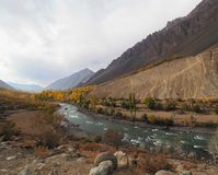 Mountains And Lake In Golden Autumn, Ghizer Valley, Northern Pakistan. Beautiful Landscape Of Golden Autumn Mountains And Lake Along Hindu Kush Mountain Range In Stock Photos