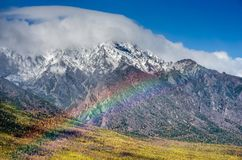 Mountains landscape with rainbow- cloudy sky in pastel colors for your design. Romantic seascape - seaside view with. Mountains landscape with rainbow - cloudy Stock Photos