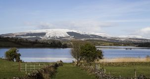 The mountains of lovely leitrim. Snow capped mountains provide the backdrop for one of lovely Leitrim`s many lakes. The mountain is called SLiave an Iariann Royalty Free Stock Photo