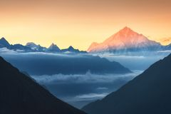 Mountains and low clouds at colorful sunrise in Nepal Stock Photo