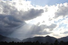 Mountains Magesty. Light streaming through clouds in front of Rocky Mountains Stock Photography