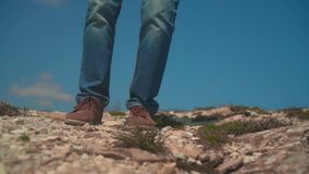 In the mountains, a man in a cowboy hat, leather jacket, blue jeans with a large tourist backpack. A man approaches, takes off his backpack and sets it on the stock video footage