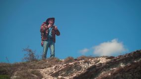 In the mountains, a man in a cowboy hat, leather jacket, blue jeans, a large tourist backpack on his shoulders. The man looks around, taking off his glasses stock video footage