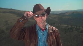 In the mountains, a man in a cowboy hat, leather jacket, glasses. A man touches his hat with his hand. In the mountains, a man in a cowboy hat, leather jacket stock footage