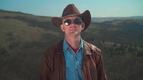 In the mountains, a man in a cowboy hat, leather jacket, glasses. A man touches his hat with his hand. In the mountains, a man in a cowboy hat, leather jacket stock video