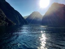 Bright Sun Reflecting on the Sea Surrounded by Mountains. Mountains at Milford Sound in New Zealand surround the open sea that is reflecting the bright sun of royalty free stock photo