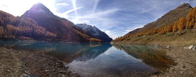 Mountains mirrored in the lake. Under blue sky Stock Photography
