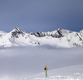Mountains in mist and warning sing on off-piste slope Stock Photos