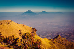 Mountains in morning fog. Photo of Mount Merbabu covered by fog near Yogya in central Java province in Indonesia. This is very remote location, rarely visited by Stock Photos