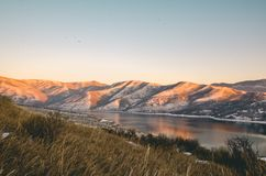 Mountains Near Lake Under Blue Sky Stock Image