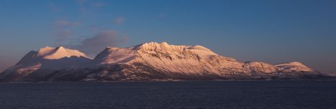 Mountains near Tromso.  Taken from shores at Bakkejord, near Tromso Norway, March 2019, sunset. Mountains near Tromso at Sunset.  Taken from shores at Bakkejord stock photos