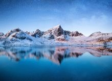 Mountains at the night time. Mountains and reflections on the water surface on Lofoten islands, Norway. Starry sky over the mounta. Ins. Winter landscape on stock images