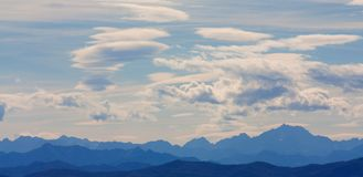 Mountains outline with many clouds stock photography