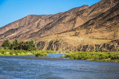 Mountains and palm groves along a river in the desert Stock Photography
