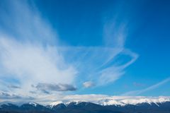 Mountains peaks and blue sky with clouds background Stock Images