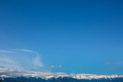 Mountains peaks and blue sky with clouds background Stock Photo