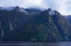 Mountains peaks in clouds on the Lake Manapouri in Fiiordland in New Zealand in the South Island in New Zealand royalty free stock images