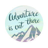 Mountains and phrase Adventure is out there in the circle. Watercolor style. Brush hand lettering Royalty Free Stock Images