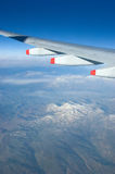 Mountains from plane. View from airplane window with high mountains with white snow hill tops and jet wing Royalty Free Stock Images