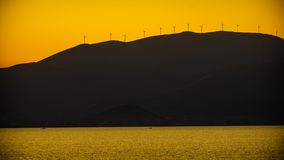 Sea view with wind turbines farm at sunset stock photos