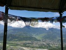 Mountains and Prayer Flags Lumbini, Nepal. Nepal Sutras, originally written on cloth banners, were transmitted to other regions of the world as prayer flags.[3] Stock Photos